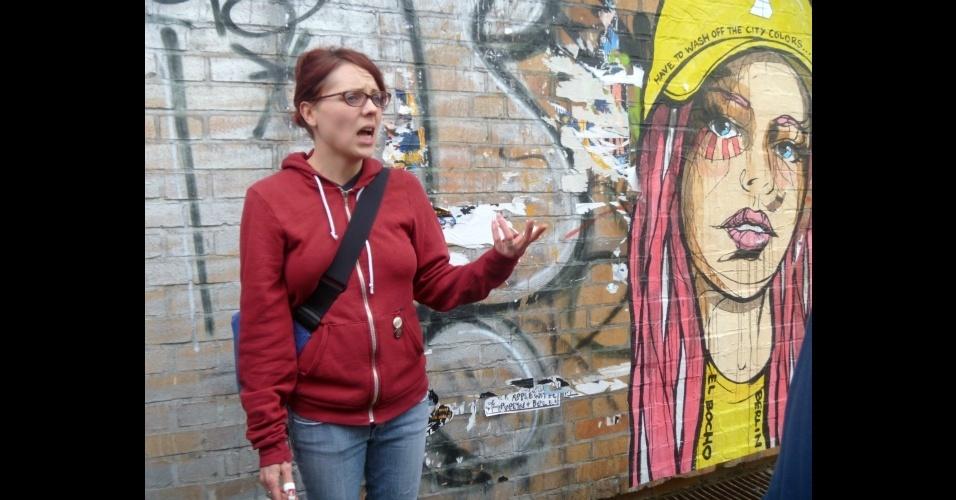 A guia Trish inicia o passeio por Berlim alternativa ao lado de um grafite do artista El Bocho