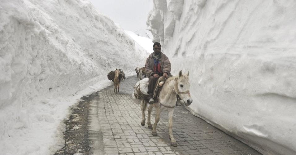 Carregadores cruzam paredes de neve ao longo da passagem Srinagar-Leh, reaberta recentemente, e que conecta a Caxemira, na Índia, à região de Ladakh, predominantemente budista