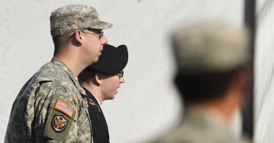 Policiais militares escoltam o soldado Bradley Manning (centro) rumo a sala do júri de Fort Meade, em Maryland (EUA). Manning, acusado de vazar informações confidenciais ao site Wikileaks, é acusado por promotores militares de auxiliar a rede Al-Qaeda