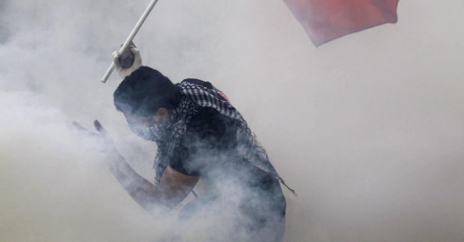 Manifestante foge de fumaça provocada por gás lacrimogêneo em Manama, no Bahrein. As ruas da capital do país estão tomadas por confrontos entre policiais e manifestantes contrários ao governo do Bahrein