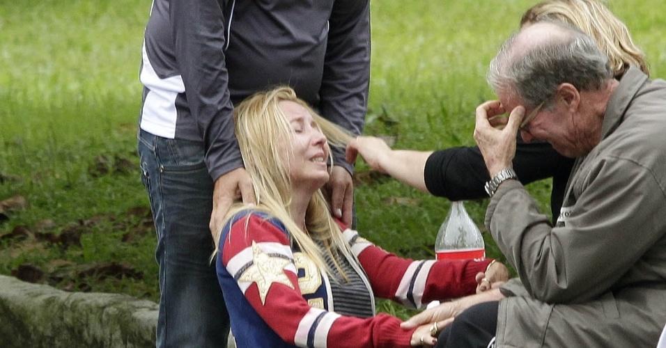27.abr.2012 - Elizabeth de Souza, mãe de uma das vítimas de acidente com monomotor, é consolada por amigos e familiares