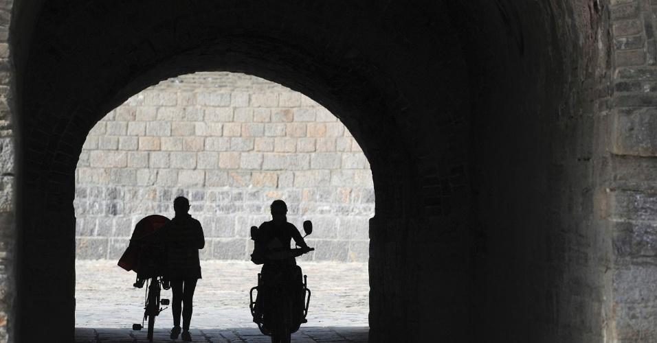 Mãe conduz criança em bicicleta através do portão da cidade de Shouxian, na China