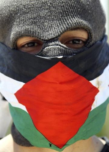 27.abr.2012- Manifestante palestino observa soldados israelenses, durante confrontos em protesto de palestinos contra construções no assentamento judeu de Qadomem, na Jordânia