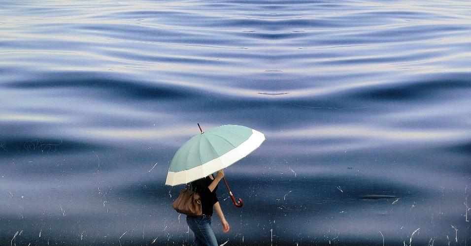 27.abr.2012- Mulher caminha na chuva no Largo de Pinheiros, zona oeste da capital paulista