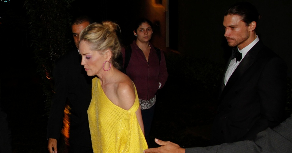 """Sharon Stone vai embora de festa acompanhada pelo modelo brasileiro Martin Mica, que ela conheceu na festa de 37 anos da revista """"Vogue"""" um dia anterior (26/4/12)"""