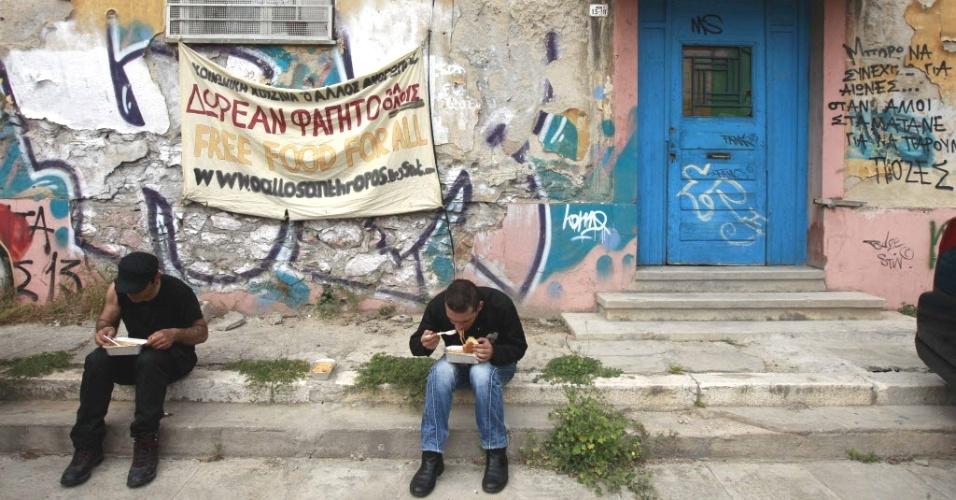 """Voluntários do grupo O Allos Anthropos (""""amigo homem"""", em tradução livre do grego) comem sopa em Atenas, capital da Grécia. Todos os dias, o grupo oferece sopa à população pobre - principalmente imigrantes e desempregados"""