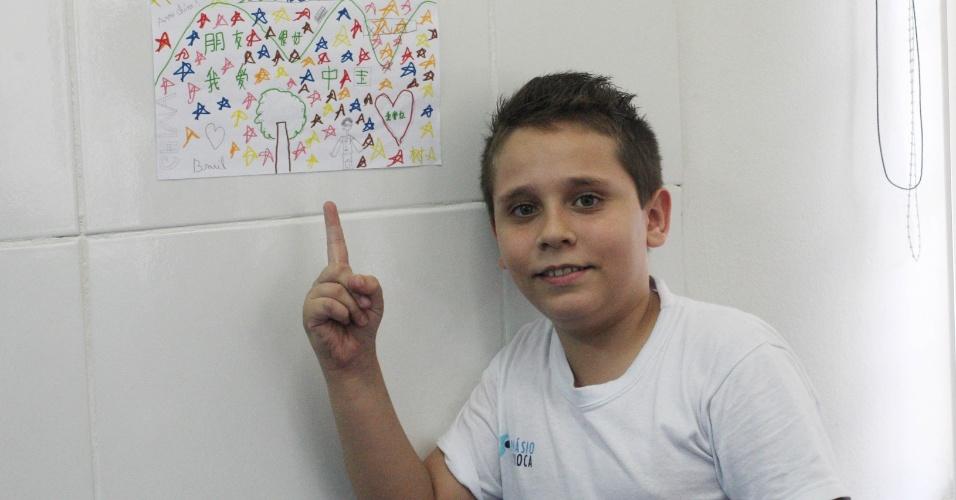 O aluno Levi Tavares, 12, do 7º ano da escola Bolívar aponta para o desenho que fez para dar as boas vindas para o novo professor de mandarim. A Bolívar é uma das três unidades municipais a oferecer eletiva de mandarim para seus alunos