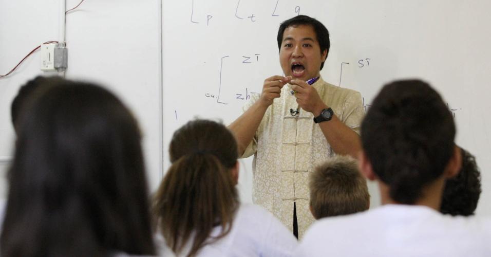 Professor Xu Lu, vestido a caráter com bata tradicional chinesa, explica aos alunos as diferenças de sons na pronúncia do mandarim