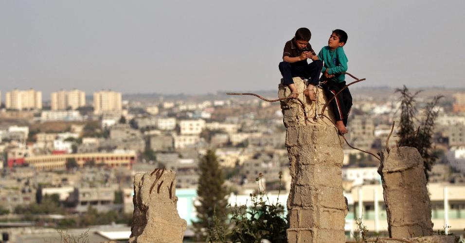 Crianças palestinas brincam entre as ruínas de uma casa destruída em Beit Lahiya, no norte da Faixa de Gaza