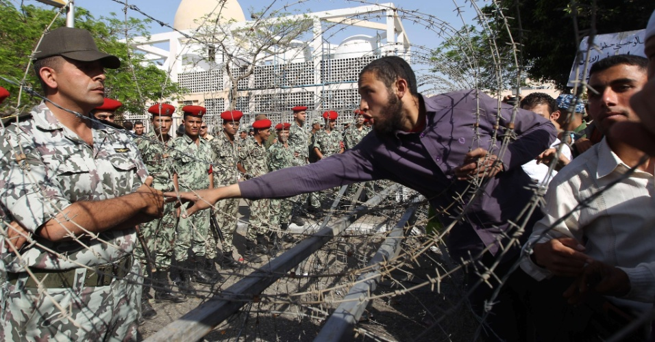Manifestante egípcio tenta falar com soldados que fazem a guarda do ministério da Defesa em Cairo, capital do Egito. A junta militar que governa o país promete entregar o poder para o presidente a ser eleito no fim de maio