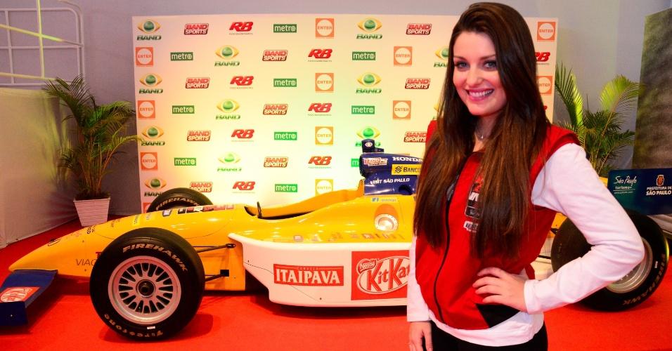 Nos camarotes da etapa de São Paulo da Fórmula Indy, modelo posa diante de carro da categoria