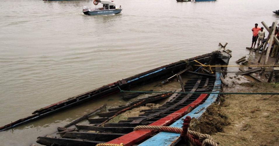 Indianos observam barco danificado após afundar no rio Brahmaputra, na Índia