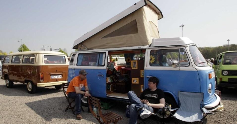 Proprietários de kombis descansam durante exposição do modelo de carro da Volkswagen em Hanover, na Alemanha
