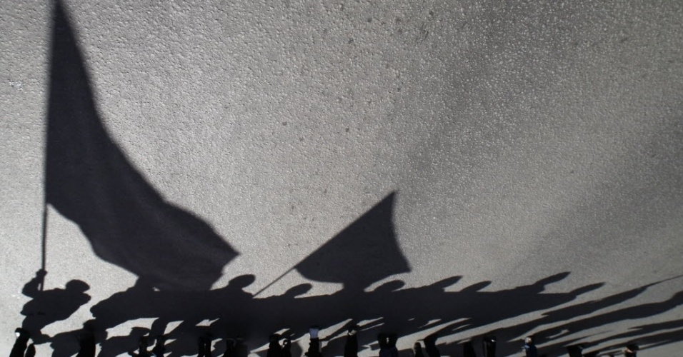 Trabalhadores fazem marcha no centro de São Petersburgo (Rússia), e suas sombras são projetadas no chão