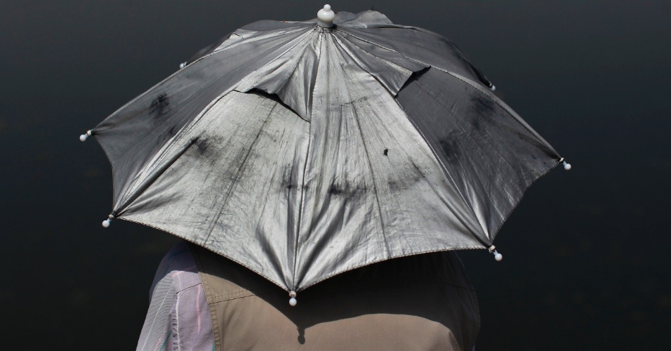 Homem segura guarda-chuva para se proteger do sol enquanto pesca no lago Houhai, em Beijing, na China