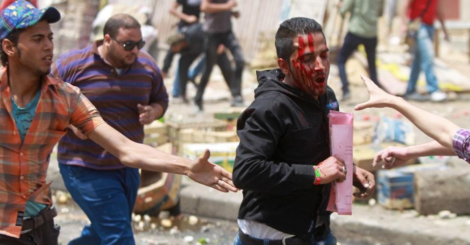 Manifestantes anti-militares correm para ajudar rapaz que foi ferido durante confrontos no distrito de Abbassiya, no Cairo (Egito). Ao menos 20 pessoas morreram, dizem autoridades locais