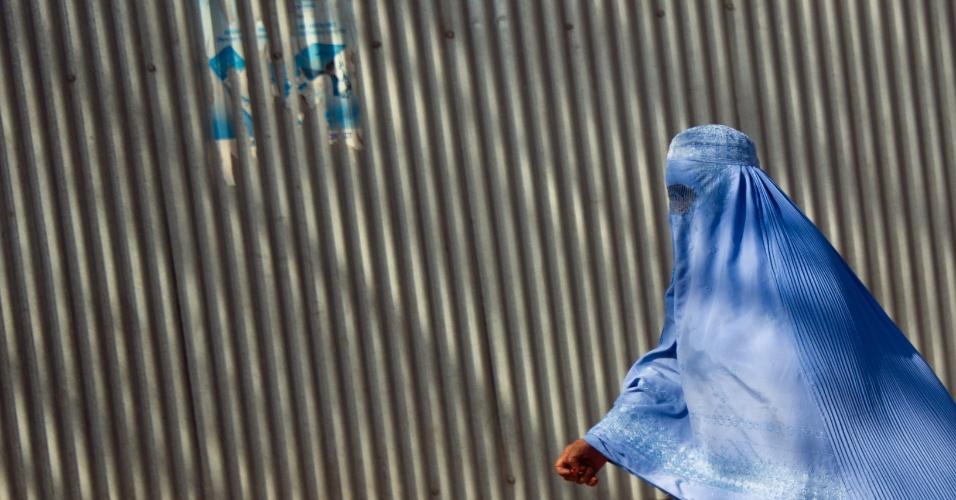 Mulher caminha em frente a muro em Cabul, no Afeganistão