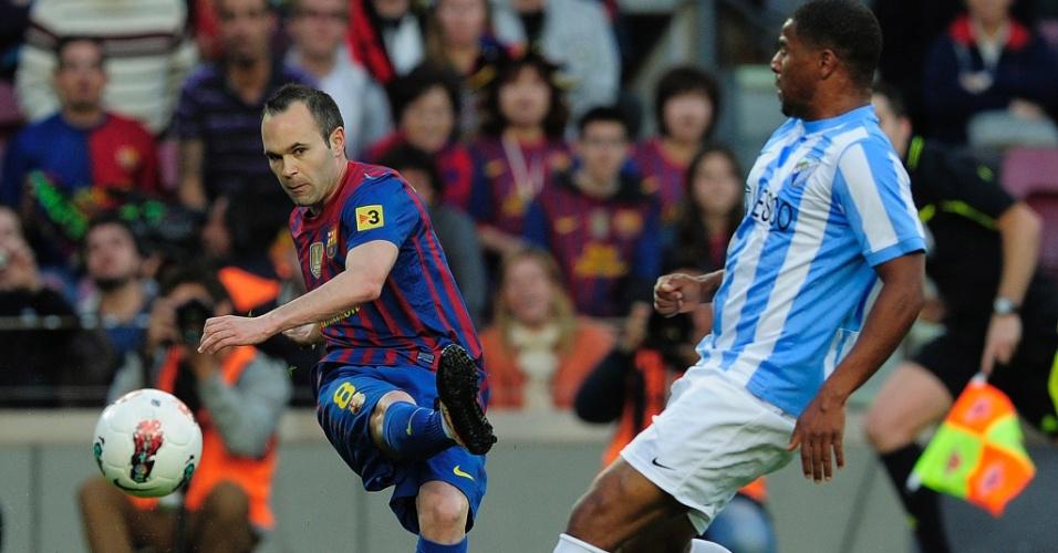 O jogador do Barcelona Iniesta chuta a bola diante da marcação de Eliseu Pereira, do Málaga