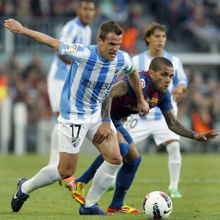 O lateral brasileiro Daniel Alves tenta passar pela marcação de Duda no Camp Nou