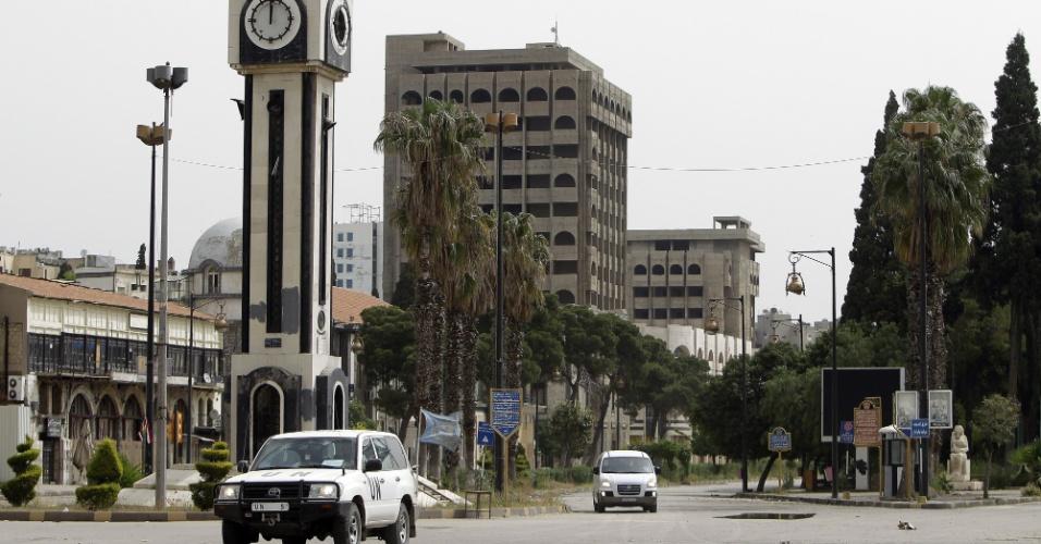 Observadores da ONU passam de carro pela praça da Torre do Relógio, em Homs, na Síria