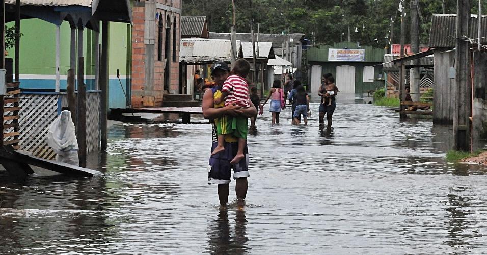 3.mai.2012 - Moradores caminham por rua castigada pela cheia do Rio Negro no bairro Nova Veneza em Cacau Pereira, distrito de Iranduba, Amazonas