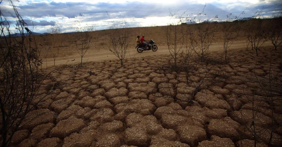 3.mai.2012 - Moradores passam de moto em frente ao rio Rio de Contas, completamente castigado pele seca, na comunidade de Porto Alegre, Bahia