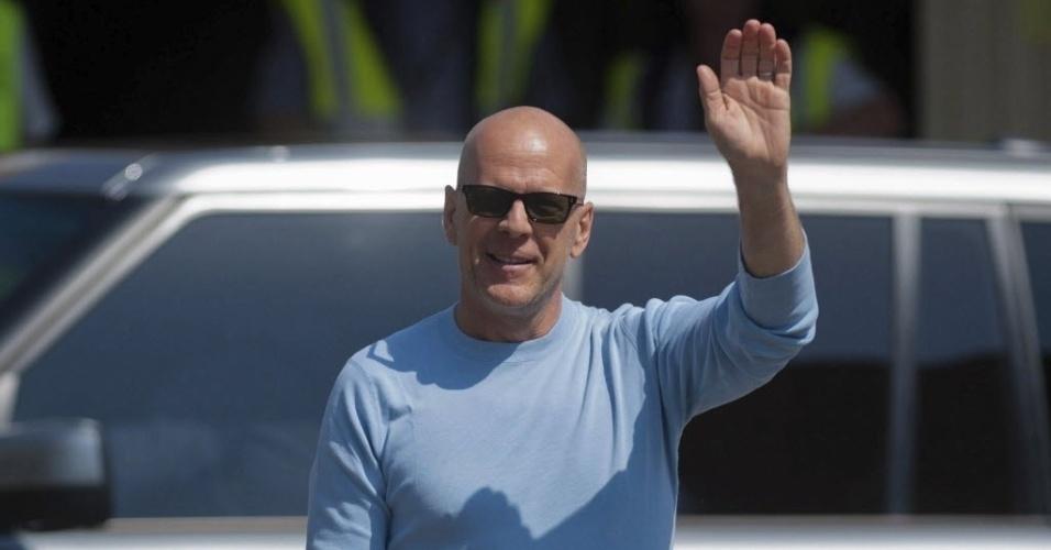 """Bruce Willis acena para fãs e paparazzi ao desembarcar em Budapeste para filmar """"Duro de Matar 5"""" (3/5/12)"""