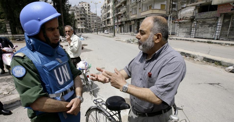Chefe do time de observadores da ONU na Síria, o coronel marroquino Ahmed Himmiche (esq.), ouve a um residente do distrito de Khalidiya, que fica em Homs