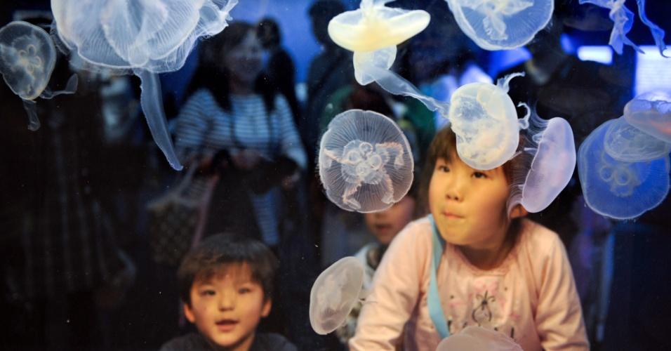 Crianças observam medusas durante visita ao Aquário de Tóquio, no Japão