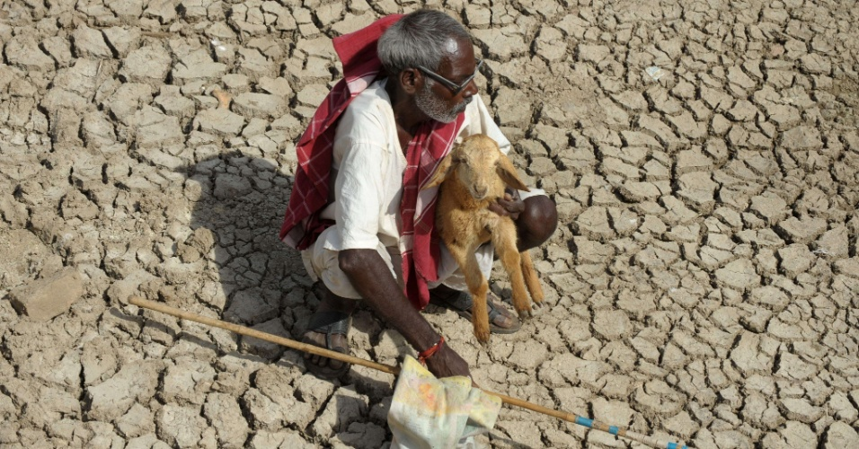 3.mai.2012 - Homem descansa com um filhote de ovelha no lago Osman Sagar, conhecido como Gandipet, nos arredores de Hyderabad, no Estado indiano de Andhra Pradesh, nesta quinta-feira (3). O lago, uma das principais fontes de água potável da região, secou, devido às altas temperaturas registradas no país