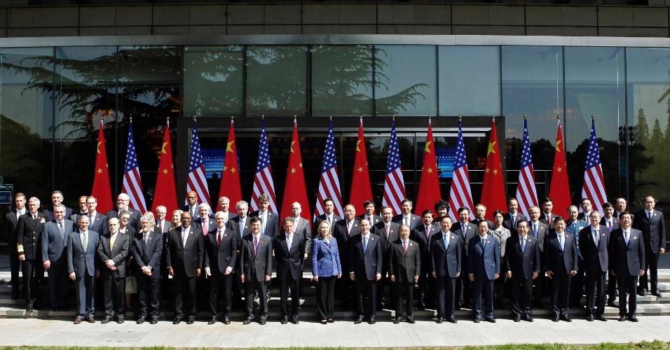 """3.mai.2012 - Participantes chineses e norte-americanos do diálogo estratégico e econômico sino-americano, entre eles a secretária americana de Estado, Hillary Clinton (centro), posam para foto, em frente a bandeiras nacionais, na Diaoyutai State Guesthouse em Pequim, capital chinesa, nesta quinta-feira (3). Hillary pediu à China que respeite as """"aspirações"""" e a """"dignidade"""" de seus cidadãos"""