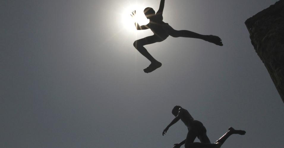 04.mai.2012 - Garotos mergulham no mar em dia quente na cidade de Chennai, na Índia. Temperaturas chegaram a 38º Celsius no país