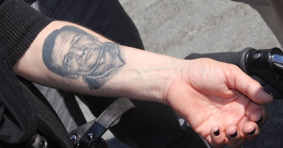 04.mai.2012 - Mulher mostra tatuagem que fez no braço, com a imagem do rosto de seu marido, que se suicidou por causa da crise econômica que atingiu a Itália. Ela participa de marcha em Bolonha, na Itália, formada por viúvas de maridos que se suicidaram