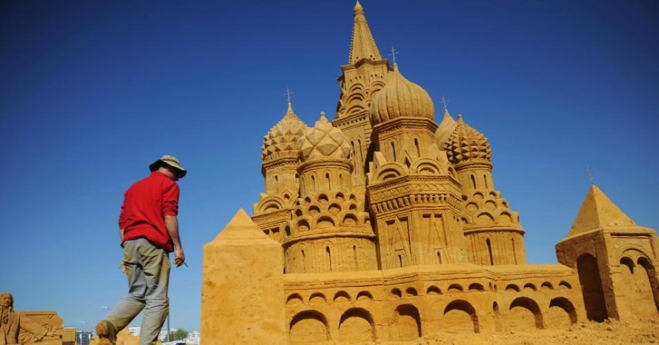 04.mai.2012 - O escultor italiano Leonardo Ugolini caminha próximo à escultura da basílica de Moscou, em exposição sobre a história da Rússia no museu a céu aberto Kolomenskoye, que fica em Moscou