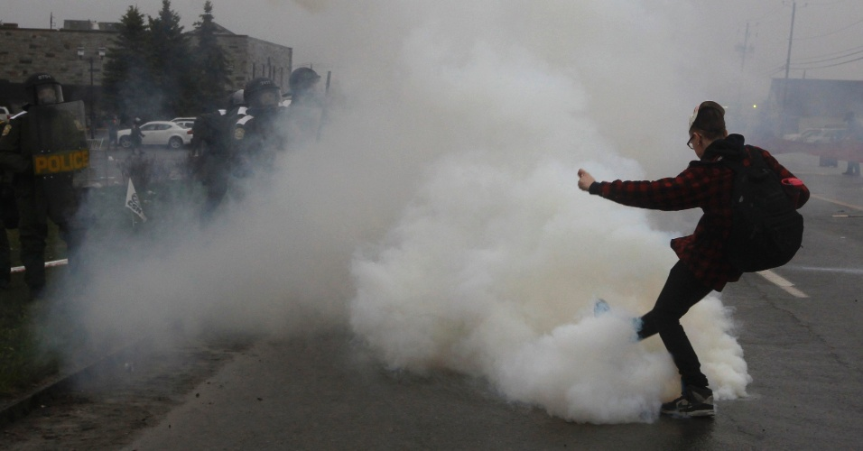 4.mai.2012 - Manifestante chuta uma lata de gás lacrimogêneo de volta para a polícia durante uma manifestação contra aumentos das mensalidades escolares em Victoriaville, Quebec, Canadá