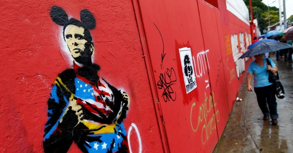 4.mai.2012 - Mulher caminha no centro de Caracas ao lado de grafite retratando o candidato de oposição à presidência da Venezuela Henrique Capriles Radonski usando uma camiseta com a bandeira dos Estados Unidos e orelhas de Mickey Mouse