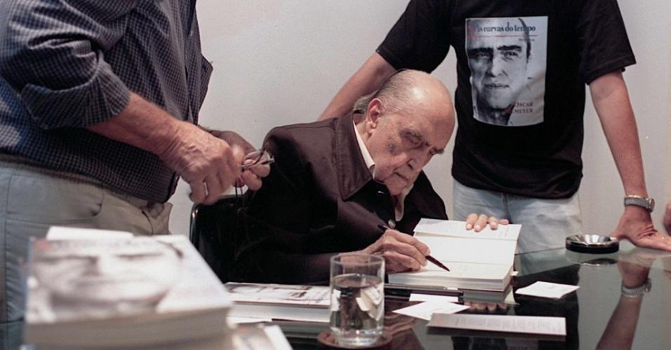 """4.mai.2012 - O arquiteto Oscar Niemeyer dá autógrafos durante o lançamento de seu livro de memórias, """"As Curvas do Tempo"""", em 1999, no Rio de Janeiro"""