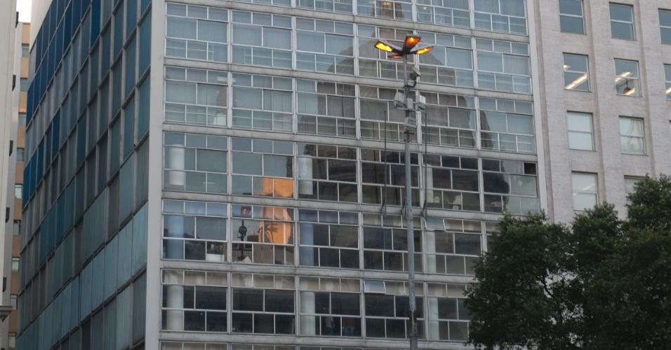 4.mai.2012 - Pessoas passam junto à fachada do edifício onde funcionou o Banco Boa Vista, no centro do Rio