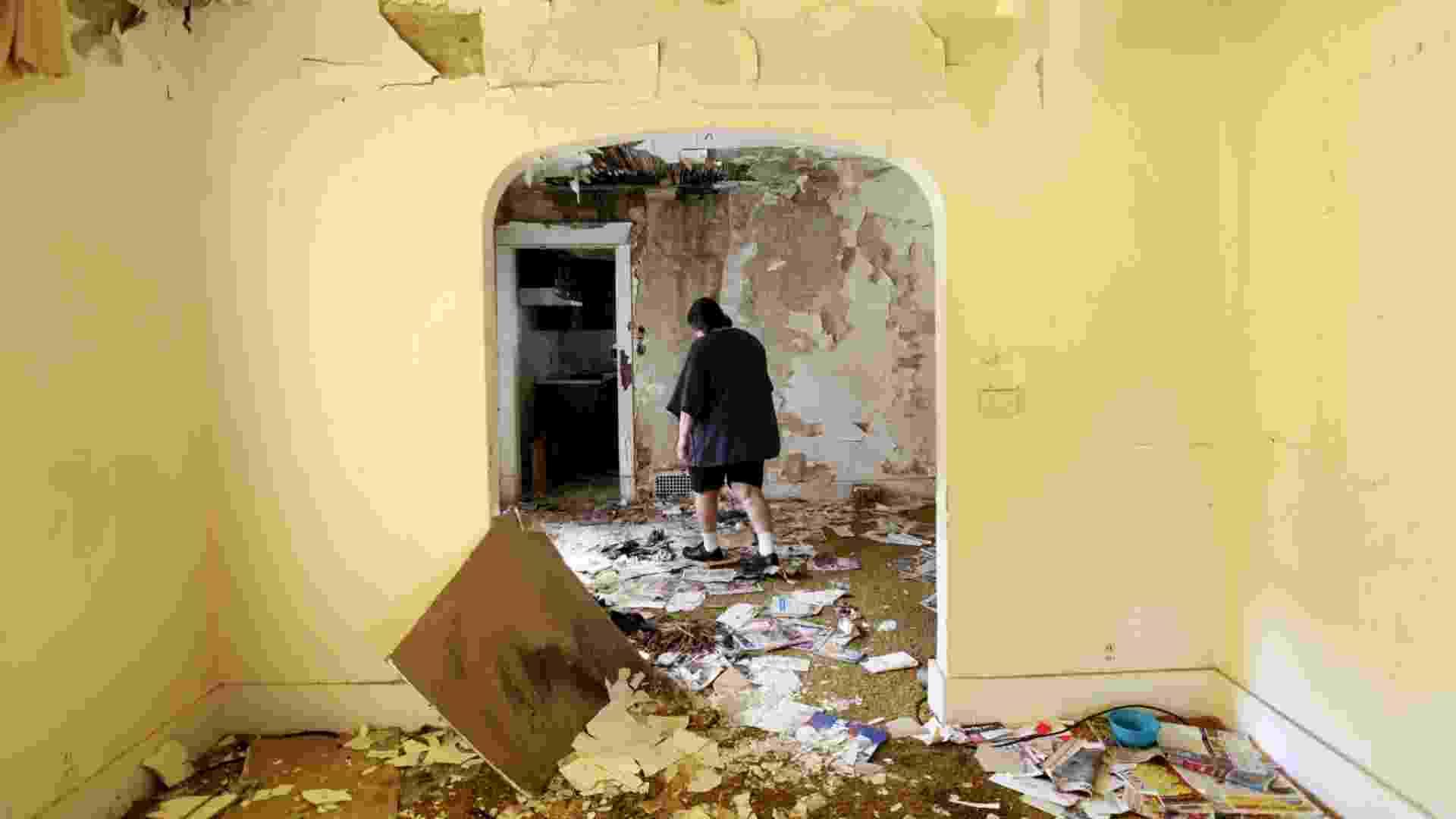 Kathy Oxian caminha por uma das casas abandonadas que comprou por US$ 750 na vizinhança de sua própria casa em South Bend, Indiana (NYT/ Não usar sem autorização) - Sally Ryan/The New York Times