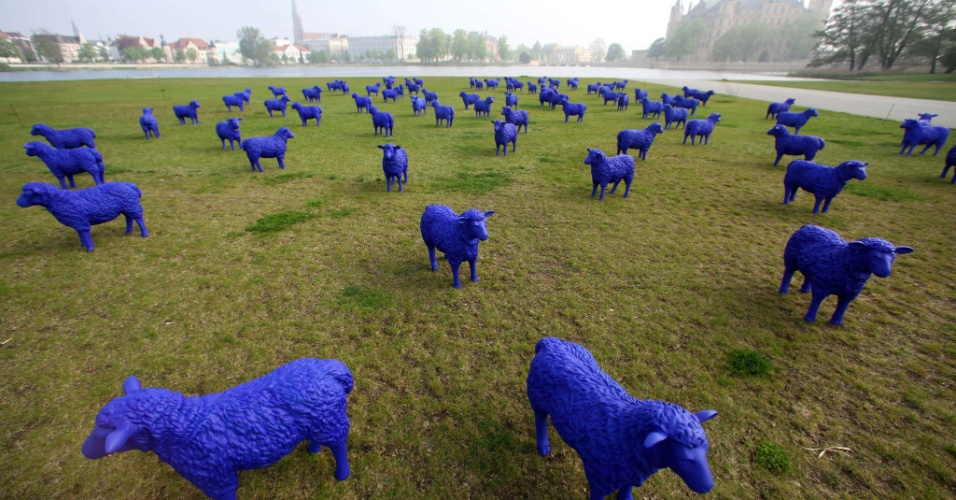 04.mai.2012 - Rebanho de ovelhas de plástico é exposto no jardim que fica em frente ao castelo de Schwerin, no norte da Alemanha. A instalação já passou por mais de 50 cidades da Europa