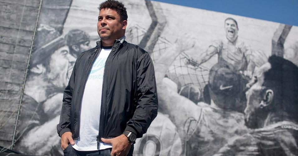 Ronaldo posa na frente de muro com imagem de comemoração de seu primeiro gol marcado pelo Corinthians