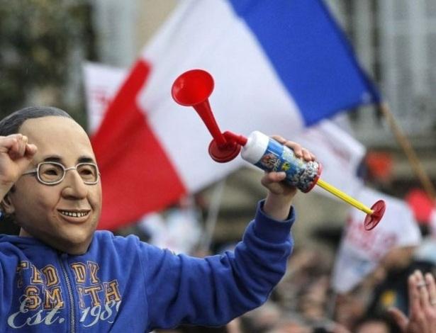 Partidário de candidato socialista François Hollande usa máscara do novo presidente da França, durante comemorações da vitória em Tulle, no sudoeste do país