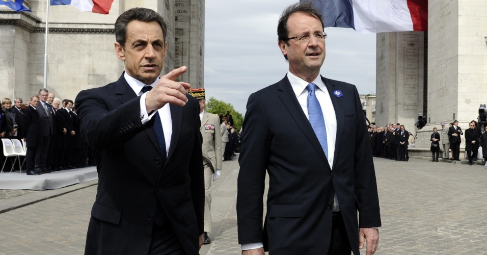 08.mai.2012 - O atual presidente francês, Nicolas Sarkozy (esq.), e o seu sucessor recém-eleito, Fraçois Hollande (dir.), participam de cerimônia que marca o 67º aniversário da vitória dos Aliados contra o Nazismo alemão na 2ª Guerra Mundial, no Arco do Triunfo, em Paris (França)