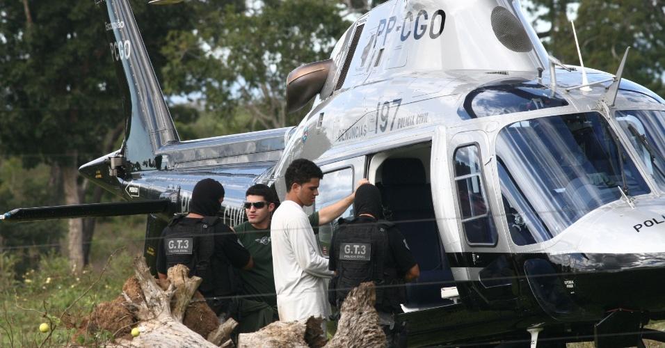 8.mai.2012 - O acusado Aparecido Alves embarca em um helicóptero acompanhado por policiais momentos antes de sua queda, no município de Piranhas, em Goiás. O helicóptero participava da reconstituição de uma chacina e caiu em uma fazenda