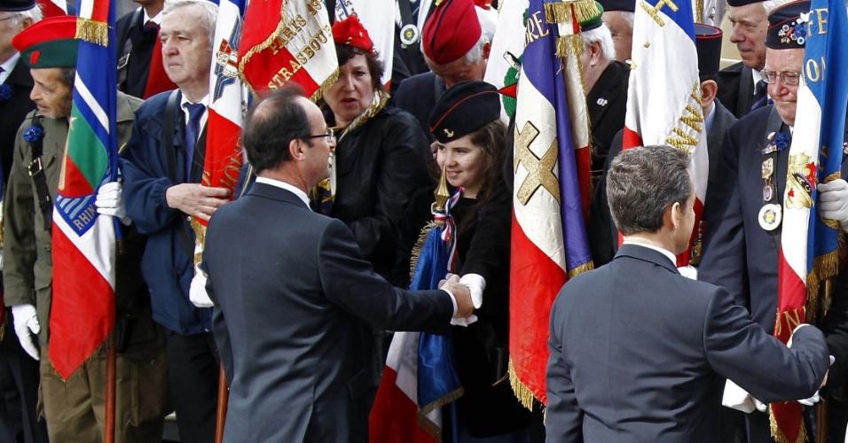 8.mai.2012 - O atual presidente francês, Nicolas Sarkozy (dir.) e o seu sucessor, François Holland (esq.), cumprimentam os veteranos da 2ª Guerra Mundial durante cerimônia em homenagem ao 67° aniversário da vitória dos Aliados sobre o Nazismo alemão, no Arco do Triunfo, em Paris