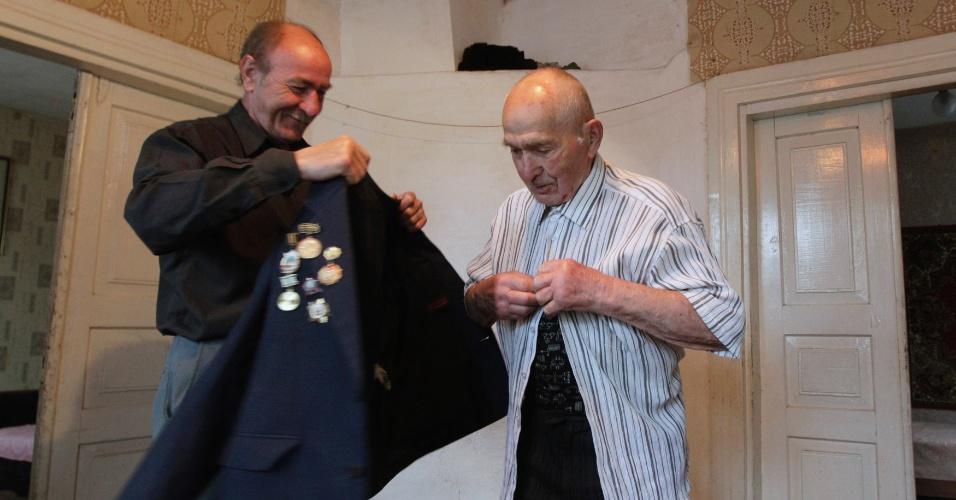 8.mai.2012 - O veterano Alexander Blotsky, 92, veste um paletó com as condecorações recebidas por seu trabalho na 2ª Guerra Mundial em sua casa, na cidade de Turov, Belarus