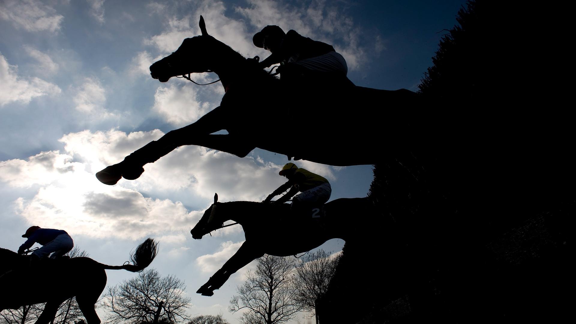 Cavalos saltam obstáculo em competição de hipismo realizada na Inglaterra, em março de 2012