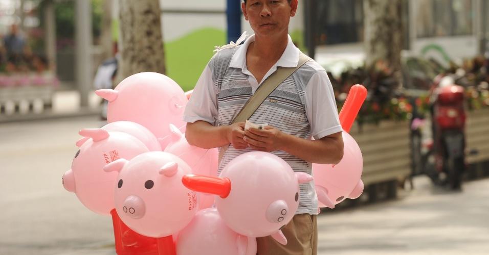 09.mai.2012 - Homem vende balões em formato de porquinhos em rua de Xangai, na China. O FMI manteve a taxa de crescimento da China acima dos 8% para este ano e o ano que vem
