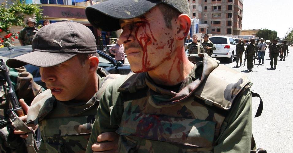 09.mai.2012 - Soldado do Exército sírio (dir.) fica ferido nesta quarta (9), após bomba ser atirada no caminhão militar em que estava, na cidade de Daraa, Síria. A explosão atingiu o veículo segundos após uma equipe de observadores da ONU passar pelo local