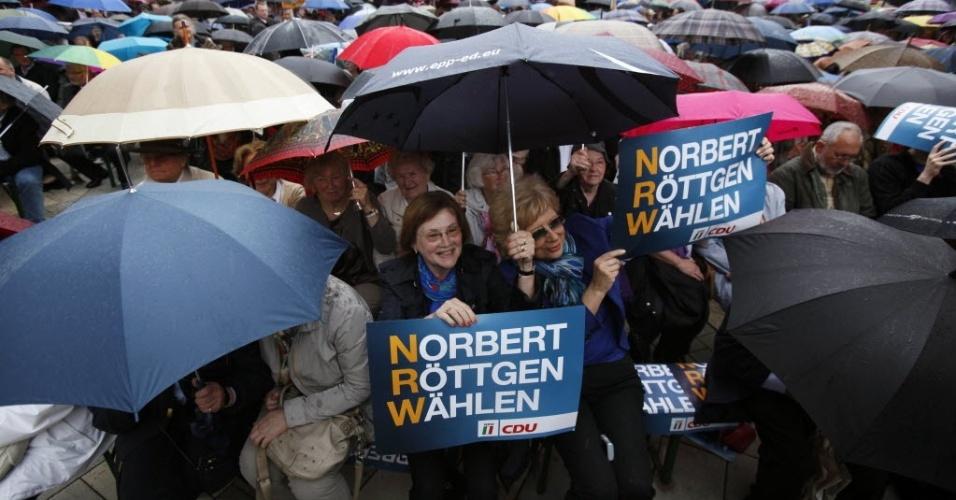 9.mai.2012 - Alemães se escondem de baixo de guarda-chuvas durante campanha eleitoral do ministro do Meio Ambiente, Norbert Roettgen, em Gelsenkirchen, na Alemanha
